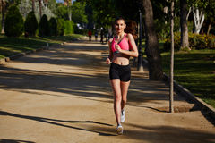 Attractive female runner in bright sportswear running in the park on beautiful palms background Stock Images