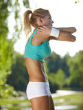 Attractive female runner stretching before her workout Royalty Free Stock Photo