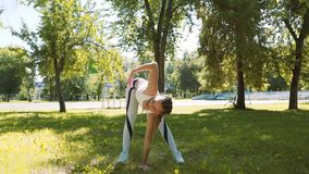 Attractive female runner stretching in summer park. Fit girl doing stretching exercise outdoors. stock footage