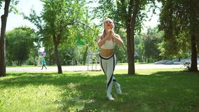 Attractive female runner stretching in summer park. Fit girl doing stretching exercise outdoors. stock video