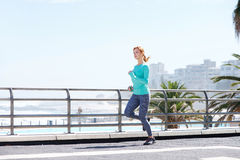 Attractive female runner training on path outdoors by sea Stock Photos