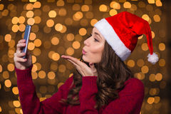 Attractive female in santa hat using smartphone and sending  kiss Royalty Free Stock Image