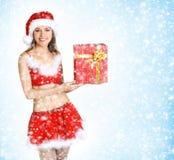 Attractive female Santa holdign a present Stock Photo