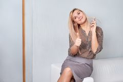 Attractive female showing thumbs up in an office stock photo