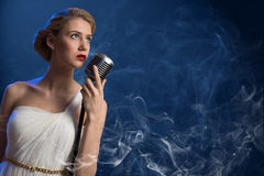Attractive female singer with microphone Royalty Free Stock Image