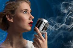 Attractive female singer with microphone Royalty Free Stock Photography