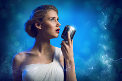 Attractive female singer with microphone Stock Photo