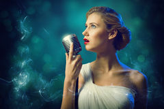 Attractive female singer with microphone Stock Image