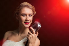 Attractive female singer with microphone Royalty Free Stock Photos
