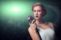 Attractive female singer with microphone Stock Images