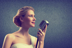 Attractive female singer with microphone Royalty Free Stock Images