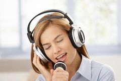 Attractive female singing with joy smiling. Young attractive female singing with joy, using microphone and headphones, smiling Royalty Free Stock Image
