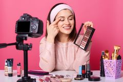 Attractive female sits in front of camera fixed on tripod. Pretty girl looks at eyeshadow which holds in hand. Successful blogger. Makes video. Lady has stock images
