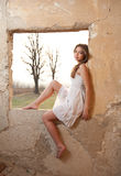 Attractive female sitting in old window frame in day light Royalty Free Stock Image