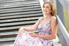Attractive female sitting on stairs outdoors with happy expression Royalty Free Stock Photos