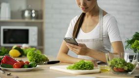 Attractive female sitting at the table and reading salad recipe on cellphone royalty free stock photos