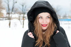 Attractive female smiling wearing hood and winter clothes Royalty Free Stock Image
