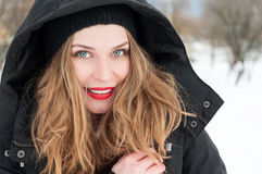Attractive female smiling wearing hood and winter clothes Stock Images