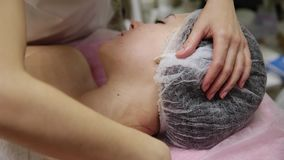 Attractive female at spa health club getting a facial massage. Beautician doing massage of face, neck and shoulders of. Beautyful young woman at luxury beauty stock video
