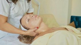 Attractive female at spa health club getting a facial procedure and massage royalty free stock images