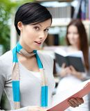 Attractive female student at the library against bookshelves Royalty Free Stock Images