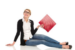 Attractive female student sitting on the floor with ring binder. Royalty Free Stock Photography