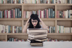Attractive female student stress looking at books in library Royalty Free Stock Photography