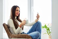 Attractive female student taking selfie with a cup of coffee in her hand royalty free stock photos