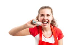 Attractive female supermarket employee biting delicious salami. Attractive young female supermarket or retail employee biting delicious salami as food royalty free stock photo