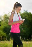 Attractive female taking a break after jogging Royalty Free Stock Photography