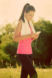 Attractive female taking a break after jogging Stock Photography