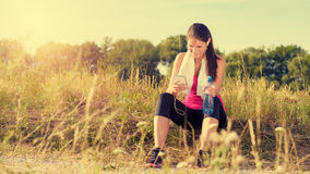 Attractive female taking a break after jogging Royalty Free Stock Images