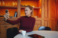 Attractive female taking photo with cell telephone digital camera while waiting for someone in coffee shop Royalty Free Stock Image