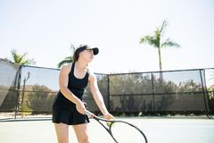 Practicing tennis ball service on court. Attractive female tennis player holding racket and ball practicing service on open court Stock Photography
