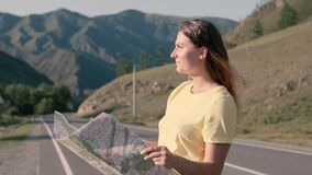 Attractive female tourist with a map in hand is standing on the highway and looking for a route for travel. Attractive female tourist with long hair with a map stock footage