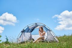 Woman tourist in the camping in the morning. Attractive female tourist posing at tent entrance, on the top of a hill against blue sky and clouds, smiling royalty free stock images