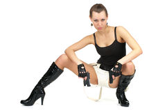 Attractive female with two guns. Attractive female sitting with two guns isolated over white Stock Photo