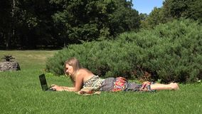 Attractive female using laptop in the park lying on the green grass. 4K stock video