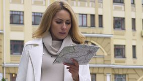 Attractive female using paper map to navigate in unknown area, destination. Stock footage stock footage