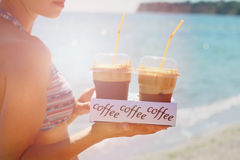 Attractive female waiters holding two ice frappe coffee on the beach near sea. Young woman enjoyng during summer holiday Stock Image