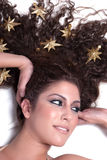 Attractive female woman's face with gold stars on her hair Stock Images