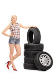 Attractive female worker standing by a stack of tires Stock Images