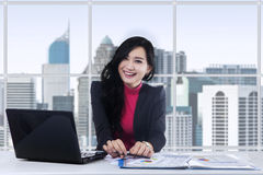 Attractive female worker working in office Stock Images