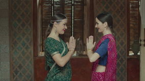 Smiling women in indian sari greeting each other. Attractive females in colorful ethnic hindu sari with bindi, tika decoration, bracelets welcoming each other stock video