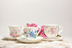 Attractive fine bone china tea cups on a neutral background. Vintage style tea party cups and saucers with flowers and lace in soft pink and blue colors on a royalty free stock images