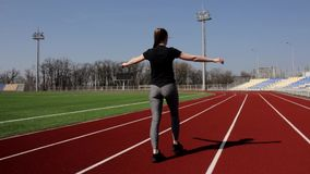 Attractive fit active young girl walking doing squats warming up stretching muscles outdoor working out at big stadium stock video footage