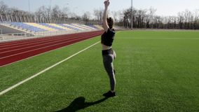 Attractive fit active young woman does yoga stretch pose on huge stadium green grass meditating calmly on warm sunny day stock video footage