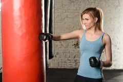 Attractive fit blond girl in light blue tank top is hitting the red punching bag . Stock Photography