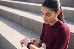 Attractive fit brunette looking at watch royalty free stock photography