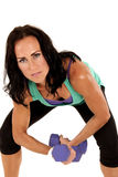Attractive fit brunette woman holding barbells leaning forward Royalty Free Stock Photo